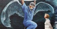 Женщина любуется граффити работника здравоохранения. Архивное фото
