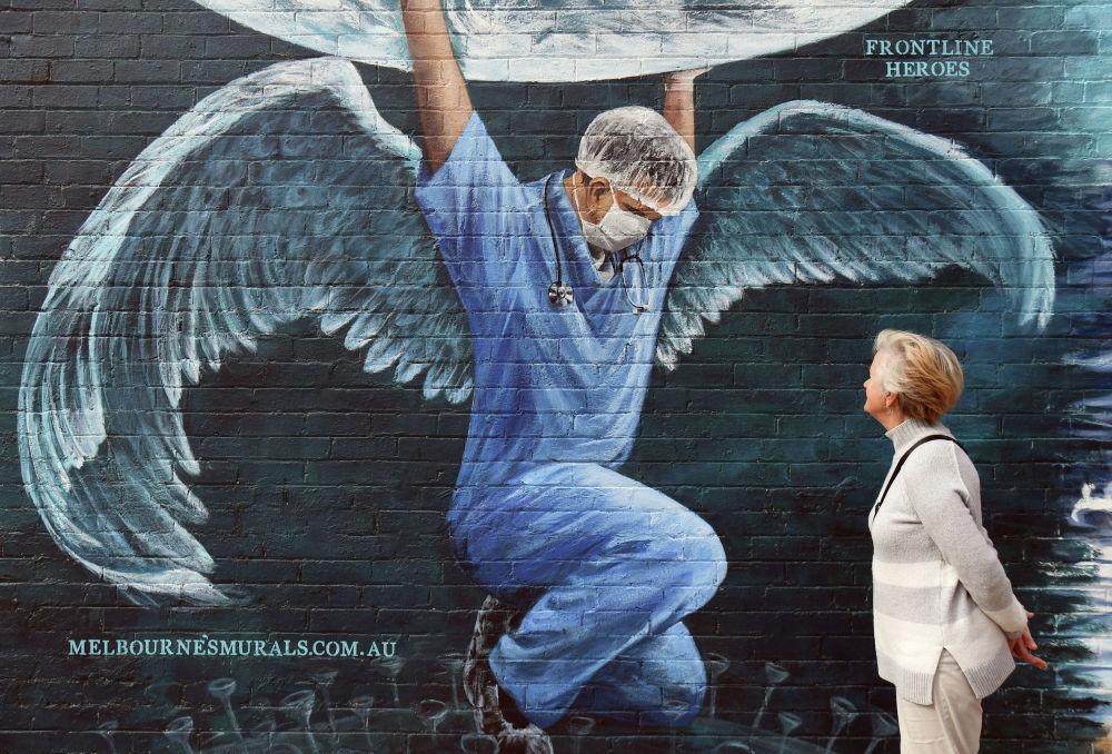 Женщина смотрит на фреску работника здравоохранения с крыльями, держащего земной шар в Международный день медсестер в Мельбурне 12 мая 2020 года