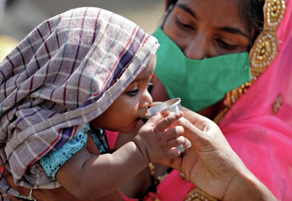 Ребенок пьет воду пока мама ждет свою очередь, чтобы сесть в поезд в железнодорожном вокзале в индийском штате Уттар-Прадеш. 15 мая 2020 года