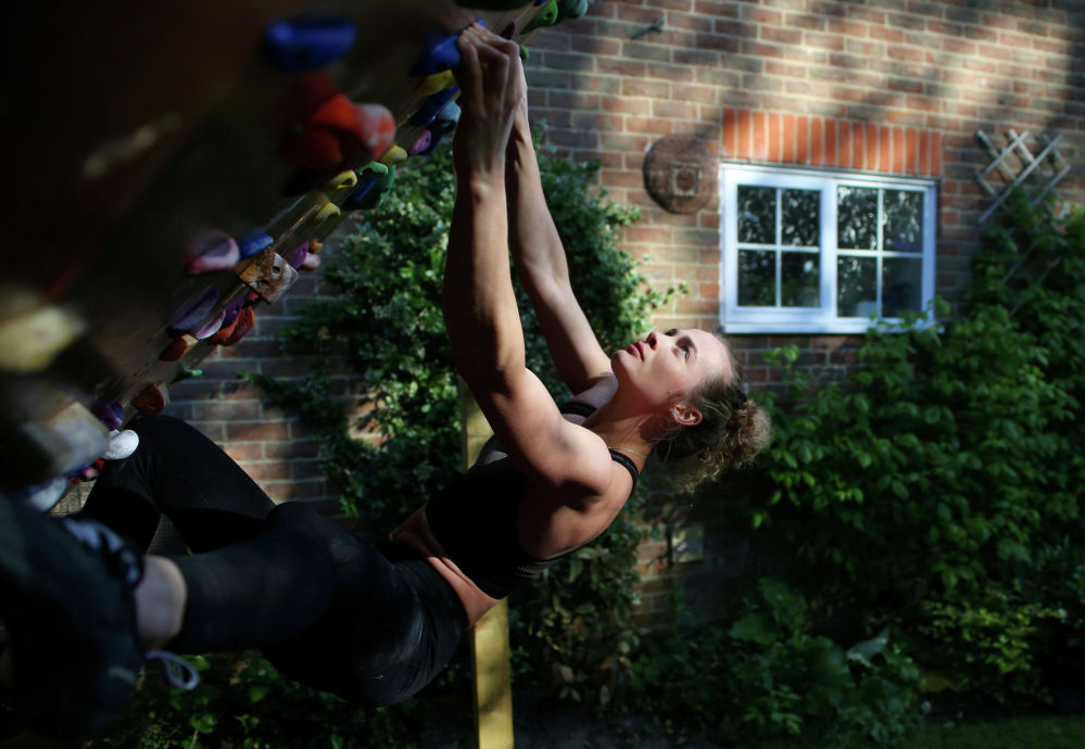 Альпинистка тренируется на стене для скалолазания у себя дома в Бордоне, Великобритания, 14 мая 2020 года