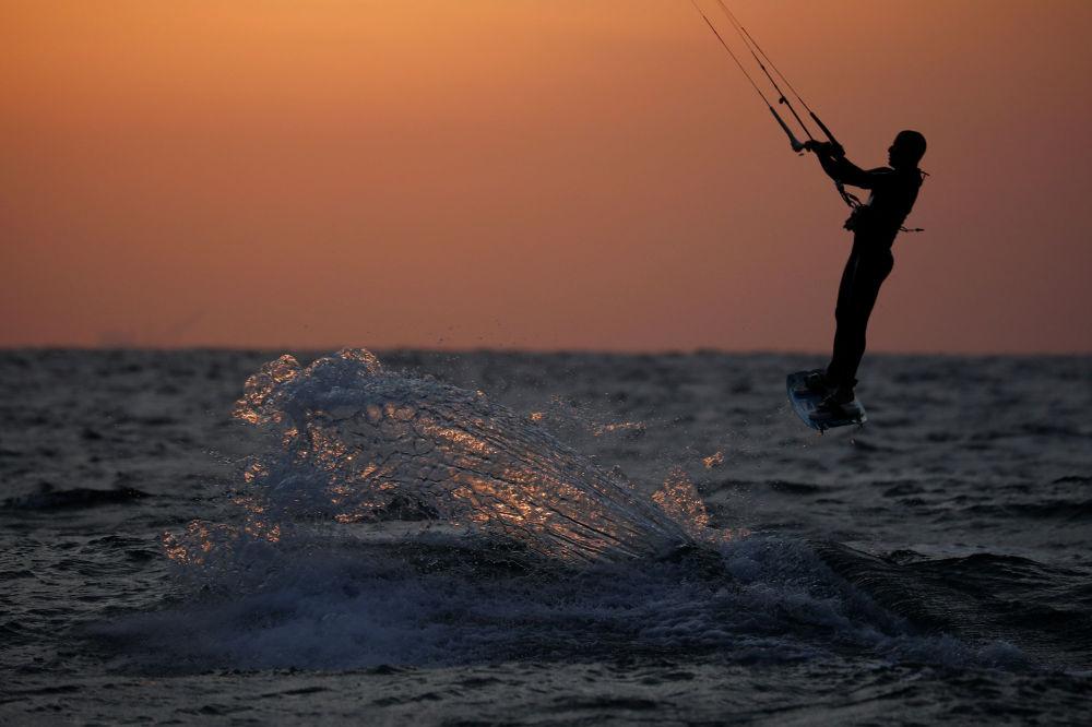 Мужчина катается на доске для кайтсерфинга на берегу Средиземного моря в Ашкелоне (Израиль). 11 мая 2020 года
