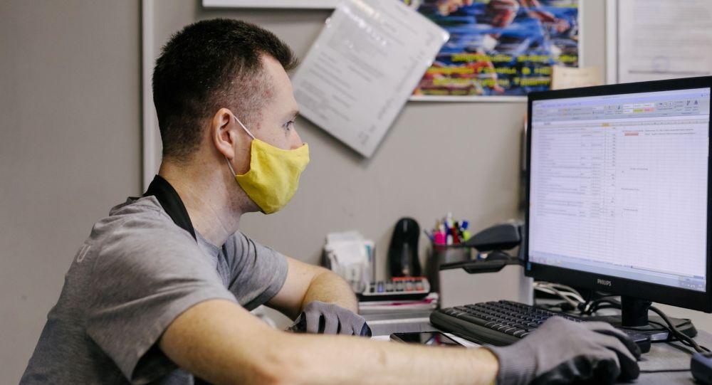 Мастер в защитной маске принимает онлайн закаы. Архивное фото