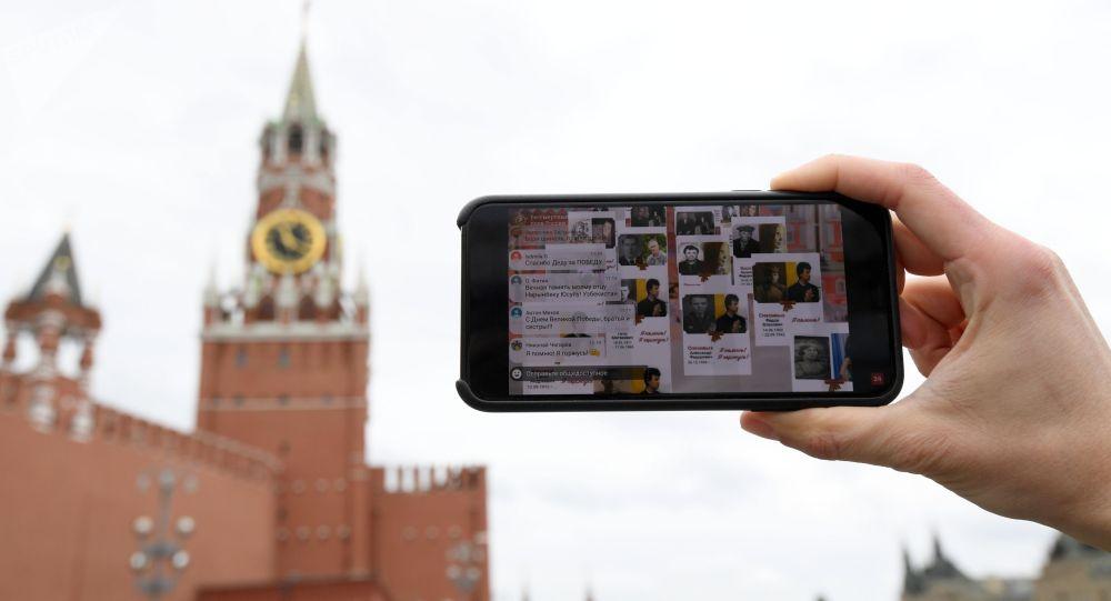 Молодой человек смотрит трансляцию акции Бессмертный полк на Васильевском спуске в Москве.
