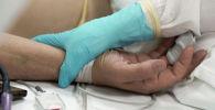 Медицинский работник у постели пациента. Архивное фото