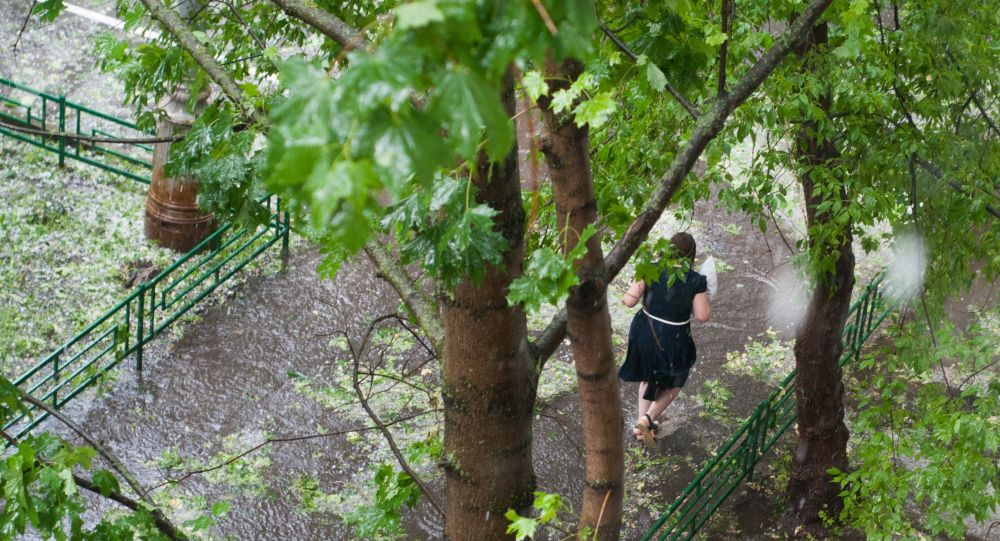 Девушка бежит по улице во время дождя и града. Архивное фото