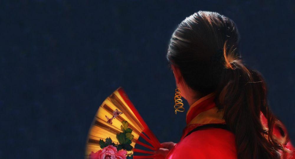 Девушка в традиционном кимоно с веером в руках