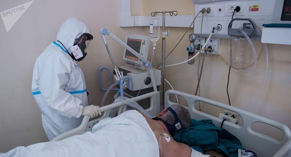 Медицинский работник возле кровати пациента в отделении реанимации. Архивное фото