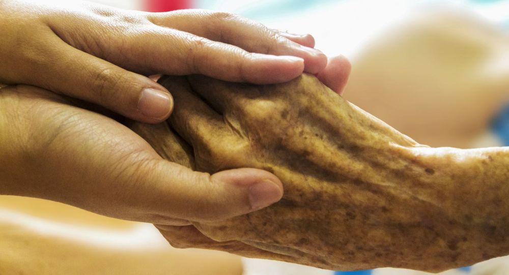 Женщина держит за руку пожилого человека. Иллюстративное фото