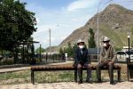 Жители Оша сидят в маске на скамейке на одном из улиц города. Архивное фото
