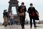 Люди в медицинских масках идут по площади Трокадеро возле Эйфелевой башни, Париж. Архивное фото