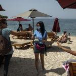 Отдыхающие в Греции платят сотруднице пляжного бара за аренду шезлонгов