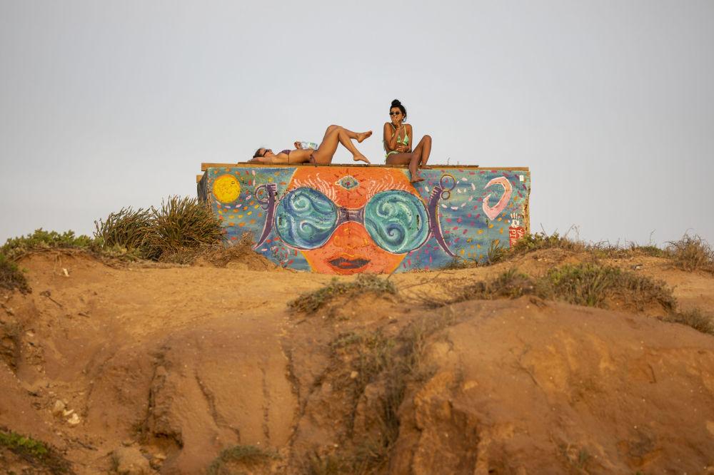 Женщины наслаждаются закатом на берегу Средиземного моря