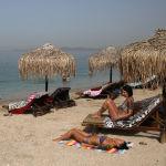 Люди загорают на пляже в Афинах