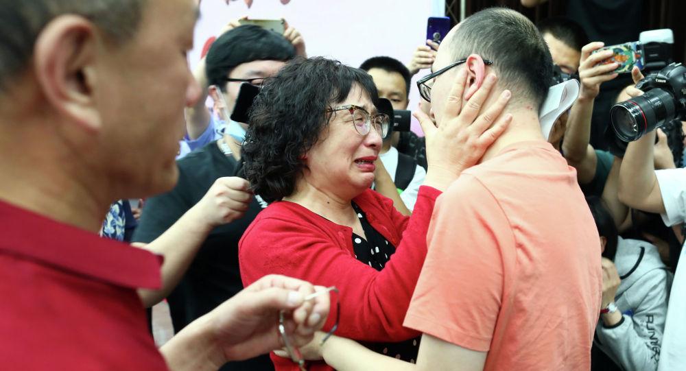 Мао Инь (справа) воссоединяется со своей матерью Ли Цзинчжи (С) и отцом Мао Чжэньпином (слева) в Сиане, в северной китайской провинции Шэньси. Китаец, которого похитили в детстве 32 года назад, воссоединился со своими биологическими родителями после того, как полиция использовала технологию распознавания лиц, чтобы выследить его. 18 мая 2020 года