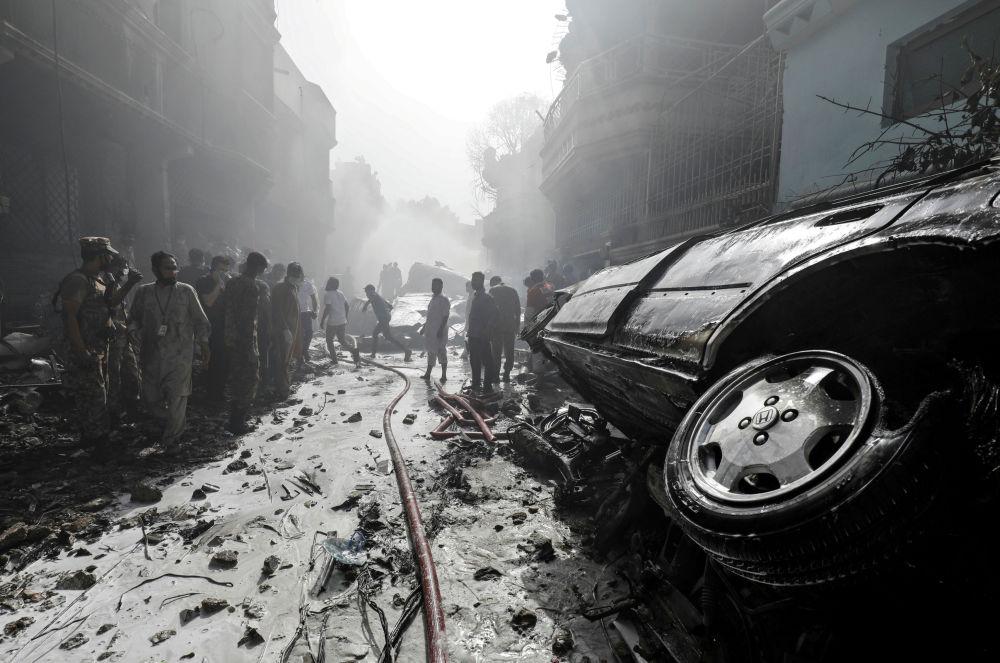 Спасатели на месте крушения пассажирского самолета в жилом районе недалеко от аэропорта в Карачи, Пакистан, 22 мая 2020 года