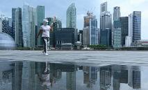 Женщина в маске гуляет по набережной в Сингапуре. Архивное фото