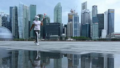 Женщина в защитной маске гуляет по набережной в бухте Марина в Сингапуре. Архивное фото