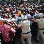 Полицейские отталкивают рабочих мигрантов перед посадкой на поезд до Султанпура в штате Уттар-Прадеш, чтобы вернуться в свои родные города после того, как правительство ослабило общенациональную блокировку, введенную в качестве превентивной меры против коронавируса COVID-19, в Амритсаре на 20 мая 2020 года.