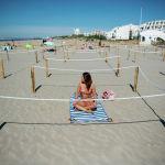 Девушка загорает на пляже Сансет-Бич в огражденной веревкой зоне, отмеченной муниципалитетом вдоль пляжей в Ла Гранд Мотт, на юге Франции, 21 мая 2020 года, поскольку страна ослабляет меры по ограничению распространения коронавируса (COVID-19), принятые для сдерживания пандемии. - Местный муниципалитет назвал эти пляжи «организованными», первыми во Франции, которые внедрили отдельные зоны для посетителей, чтобы соблюдать социальное дистанцирование.