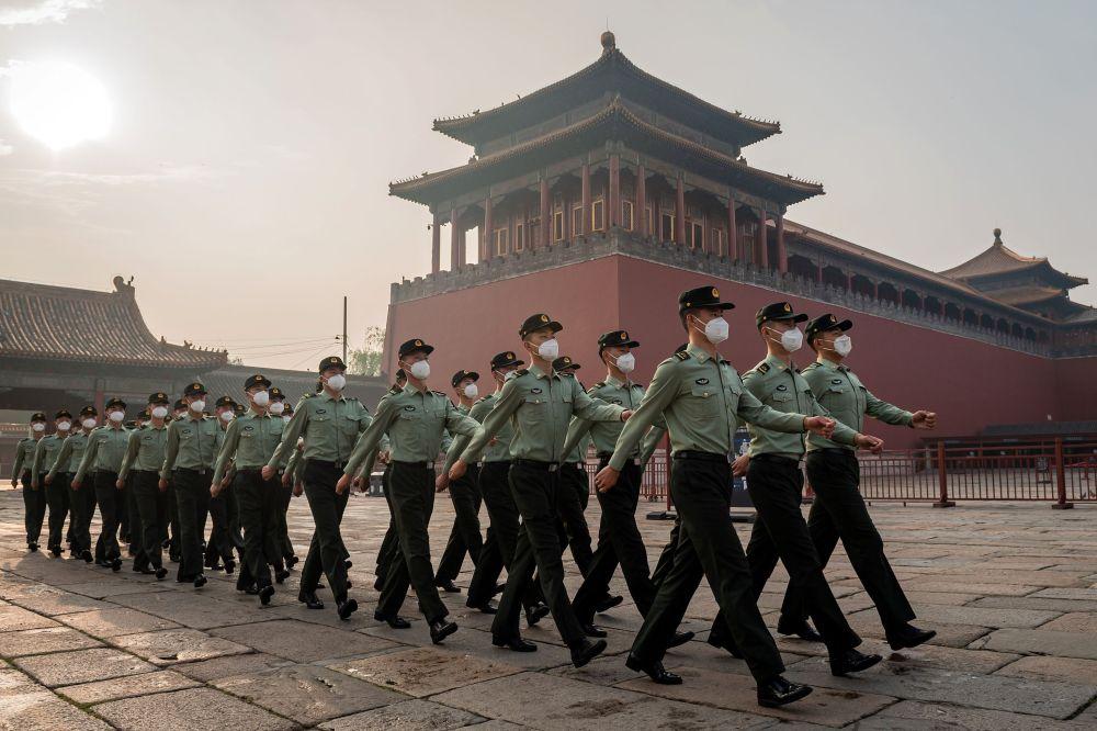 Солдаты Народно-освободительной армии маршируют возле входа в Запретный город во время церемонии открытия Китайской народной политической консультативной конференции в Пекине 21 мая 2020 года. - Крупнейшее политическое событие Китая - Национальный народный Конгресс открывается 22 мая после нескольких месяцев задержки в связи с коронавирусом, когда президент Си Цзиньпин намерен спрогнозировать силу и контроль над вспышкой, несмотря на международную критику и слабую экономикоу.
