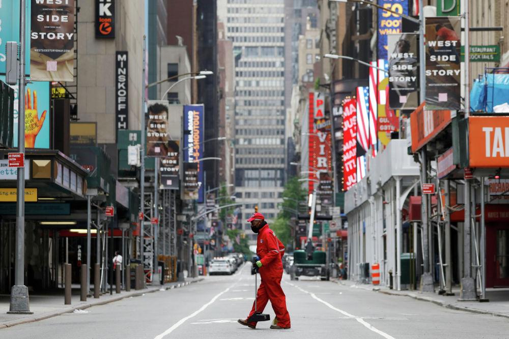 Уличный уборщик идет через закрытый театральный район Бродвея возле Таймс-сквер, после вспышки коронавируса (COVID-19) в Манхэттене, Нью-Йорк, США, 24 мая 2020 года.