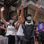 Протестующие показывают пять пальцев, обозначая Пять требований - не меньше, когда они маршируют по улице в центре города во время демократической акции протеста против пекинского законодательства о национальной безопасности в Гонконге, 24 мая 2020 года. Продемократическая лагерь партии Гонконга жестко раскритиковал попытки Китая по принятию законодательства о национальной безопасности на полуавтономной территории. Они говорят, что это идет вразрез с концепцией Одна страна, две системы, которая обещает городские свободы, которых нет на материке.