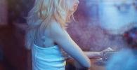 Девушка за чашечкой кофе в кафе. Иллюстративное фото