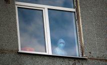 Медицинский сотрудник в окне. Архивное фото