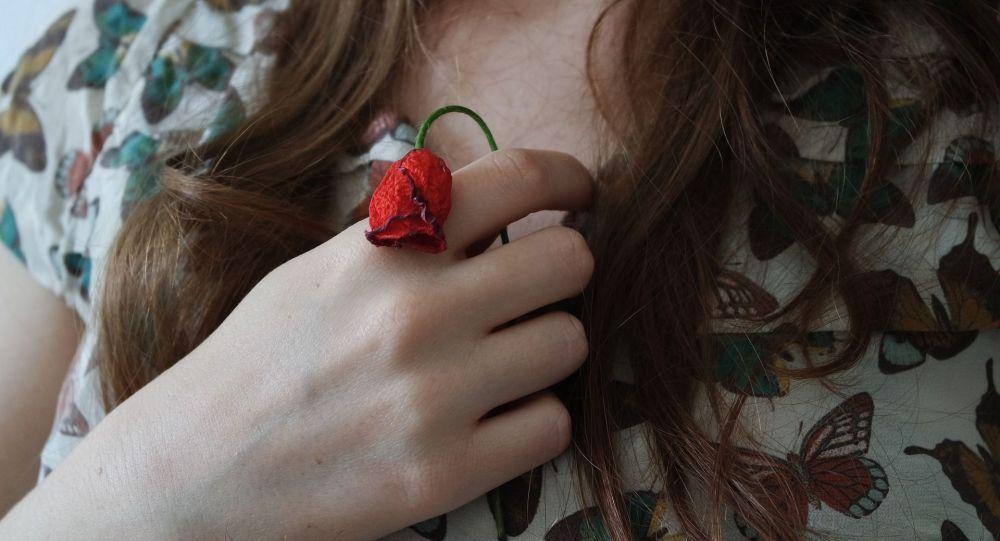 Девушка держит цветок в руке. Иллюстративное фото