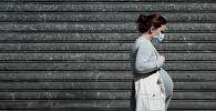 Беременная женщина на прогулке. Архивное фото