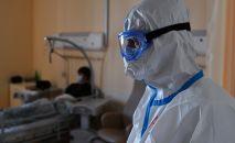 Медицинский работник возле кровати пациента. Архивное фото