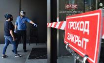 Охранник и посетитель в медицинских масках у входа в торговый центр. Архивное фото