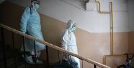 Медицинские работники во время визита к пациентам, контактировавшим с заболевшими коронавирусом. Архивное фото