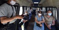 Пассажиры в маршрутке в масках в Бишкеке. Архивное фото
