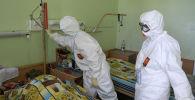 Медицинские работники осматривают пациента. Архивное фото