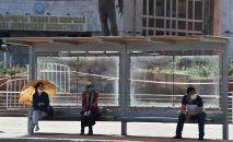 Люди в защитной маске сидят на автобусной остановке в Бишкеке на фоне вспышки COVID-19, вызванной новым коронавирусом. Архивное фото