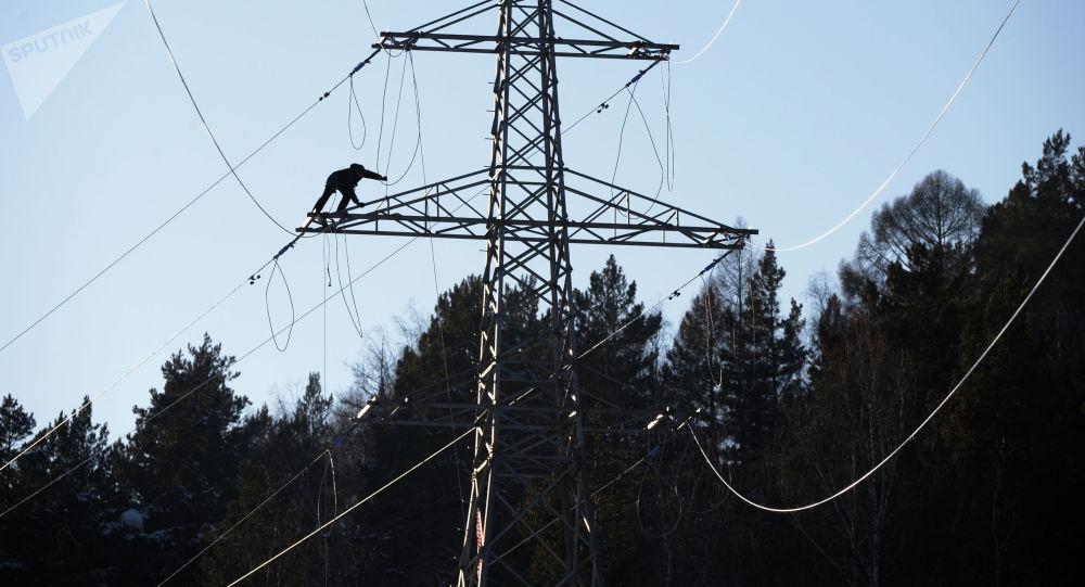 Рабочий монтирует высоковольтную линию электропередач. Архивное фото