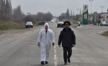 Медик и сотрудник милиции в лицевых масках идут по контрольно-пропускному пункту. Архивное фото