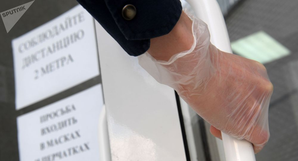 Человек в резиновой перчатке открывает дверь. Архивое фото