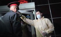 Мужчина проверяет температуру сотрудница милиции у входа в один из точек общепита в Оше