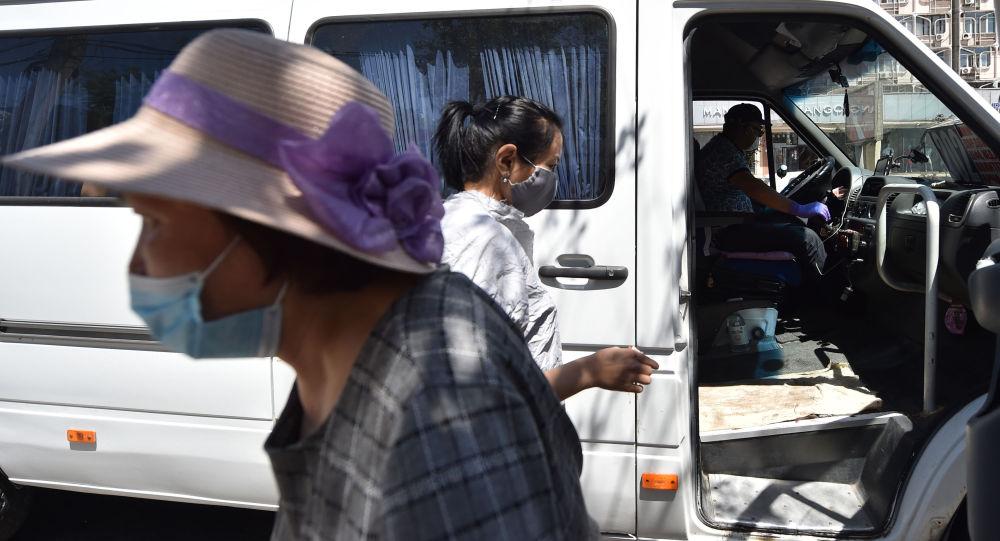 Женщины в медицинских масках садятся в маршрутку после ослабления карантинных мер в Бишкеке. 25 мая 2020 года