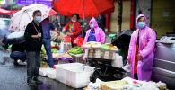 Люди в защитных масках на уличном рынке в Ухане. Архивное фото