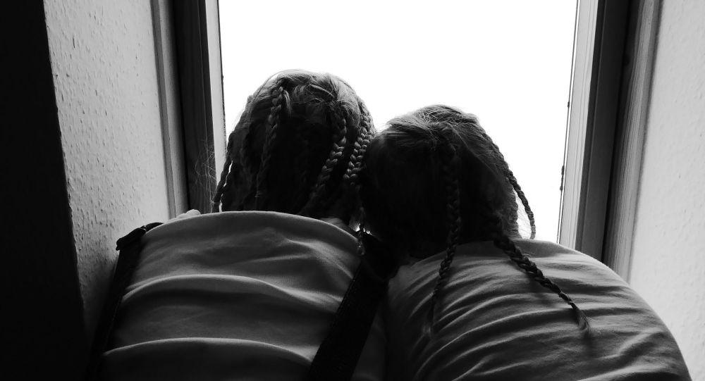 Сестры обнимаются у окна. Иллюстративное фото