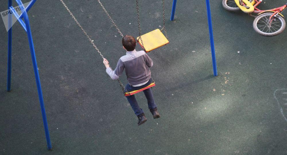 Мальчик качается на качелях. Архивное фото