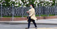 Девушка в медицинской маске идет по улице в Москве