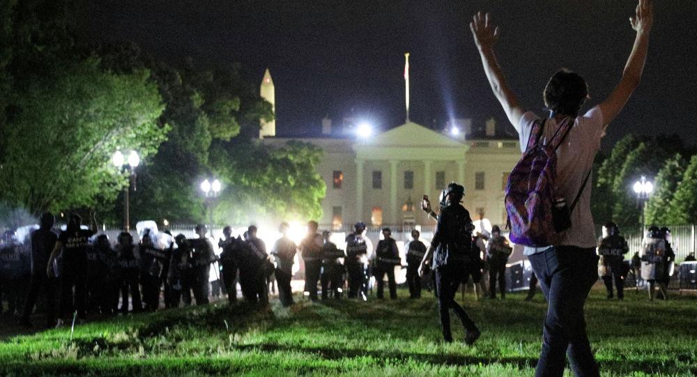 Сотрудники полиции охраняют порядок около белого дома в Вашингтоне во время массовых беспорядков в США из-за смерти афроамериканца Джорджа Флойда. 30 мая 2020 года