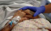 Врач держит руку пациента. Архивное фото