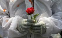 Медицинский работник держит цветок. Архивное фото