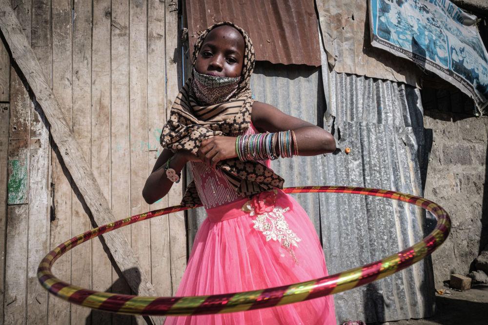 Девочка крутит обруч в центре для сирот в Найроби