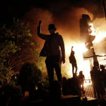 Протестующие у горящего ресторан в Миннеаполисе после убийства афроамериканца Джорджа Флойда полицейскими.
